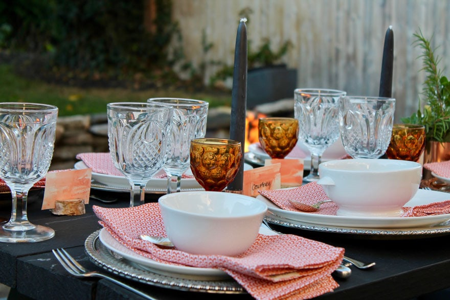 dishes, amber and clear glassware, orange napkins, gray candle