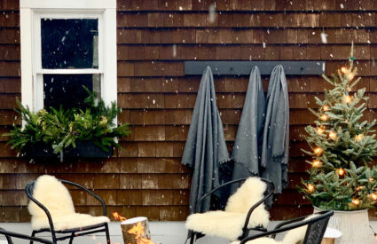 firepit, throws on hooks, chair with sheepskins, window box with greesn, snowing