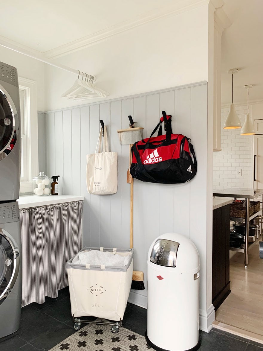 trash can, hooks on wall in laundry room, cart
