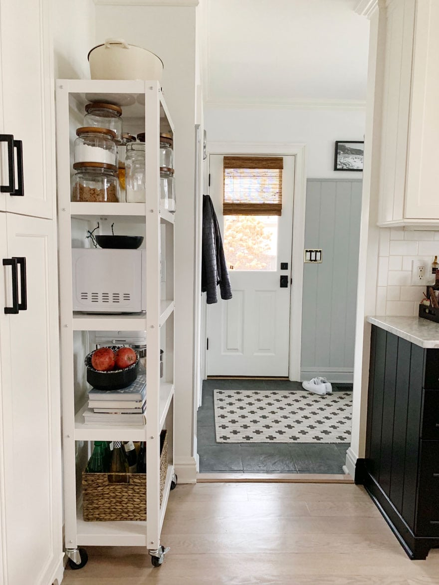 shelf with kitchen supplies, door. rug, handles on cabinets