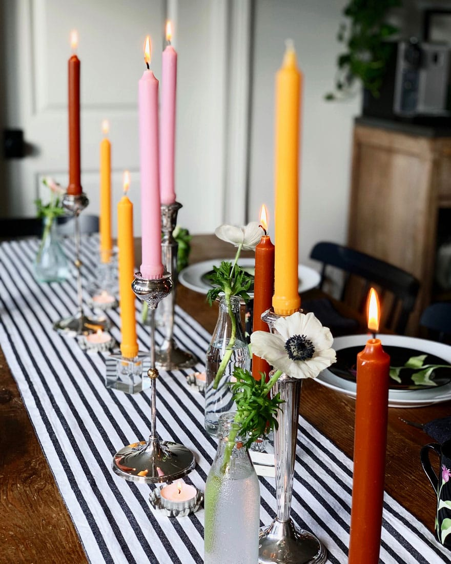differnt color candles on table with black and white runner