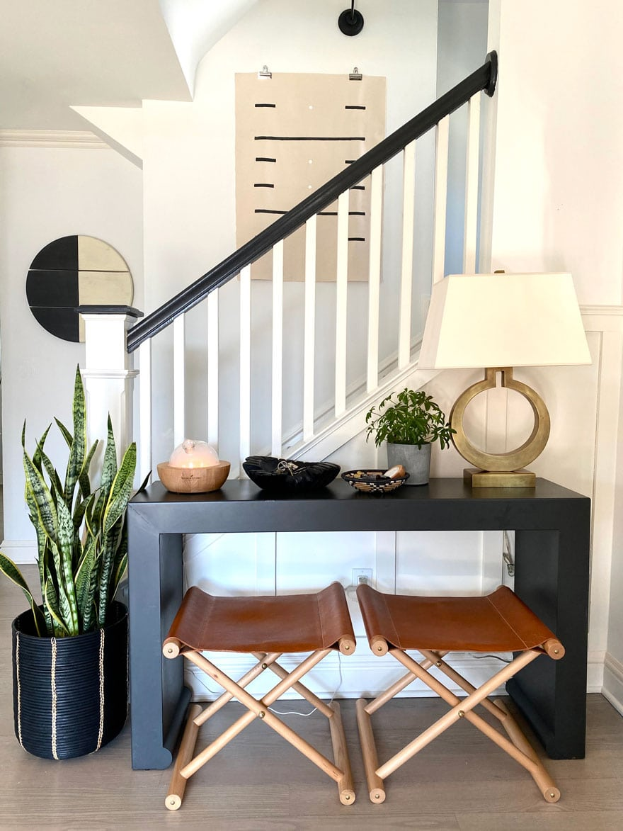 console table with camp stools and snake plant