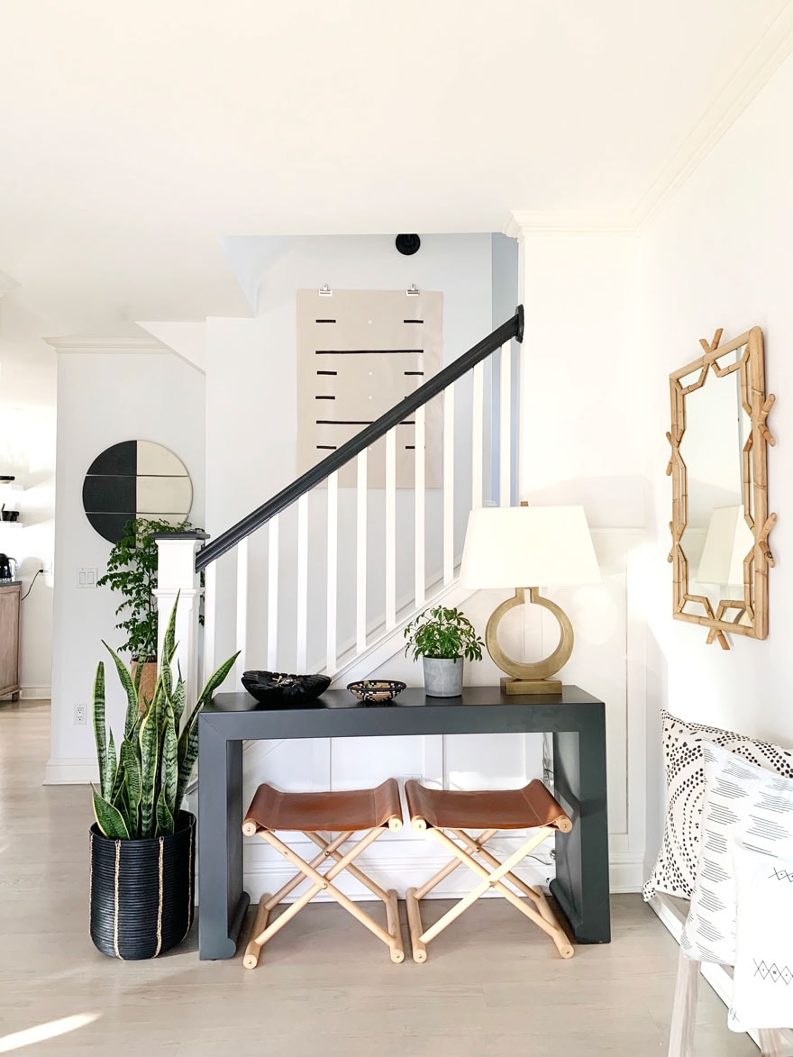 an entryway with a console table, lamp, 2 stools and mirror, snake plant