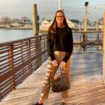 woman standing on dock wearing black sweater, pants, holding black bag, wearing eye glasses