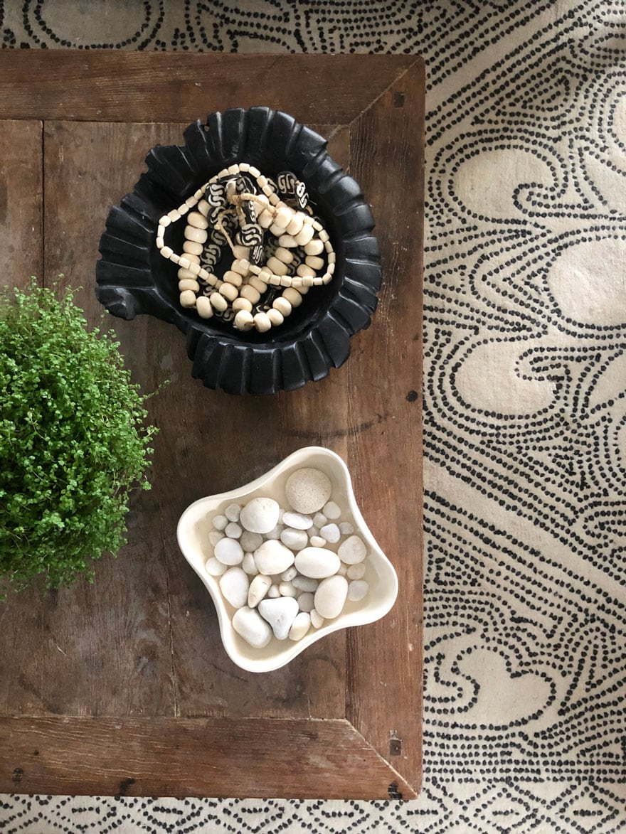 patterned rug with part of wood coffee table showing, bowl of white beach stones, plants and black wood bowl of cream colored beadfs