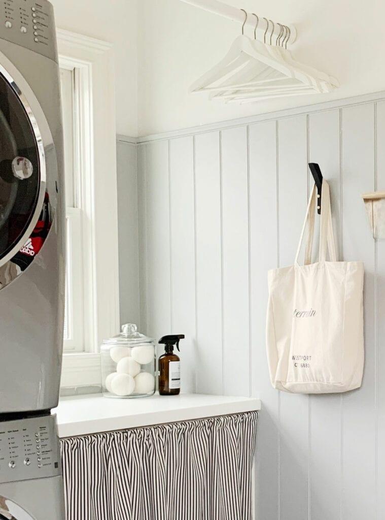 jar of wool dryer balls, cleaner amber bottle, washer/dryer bag on hook