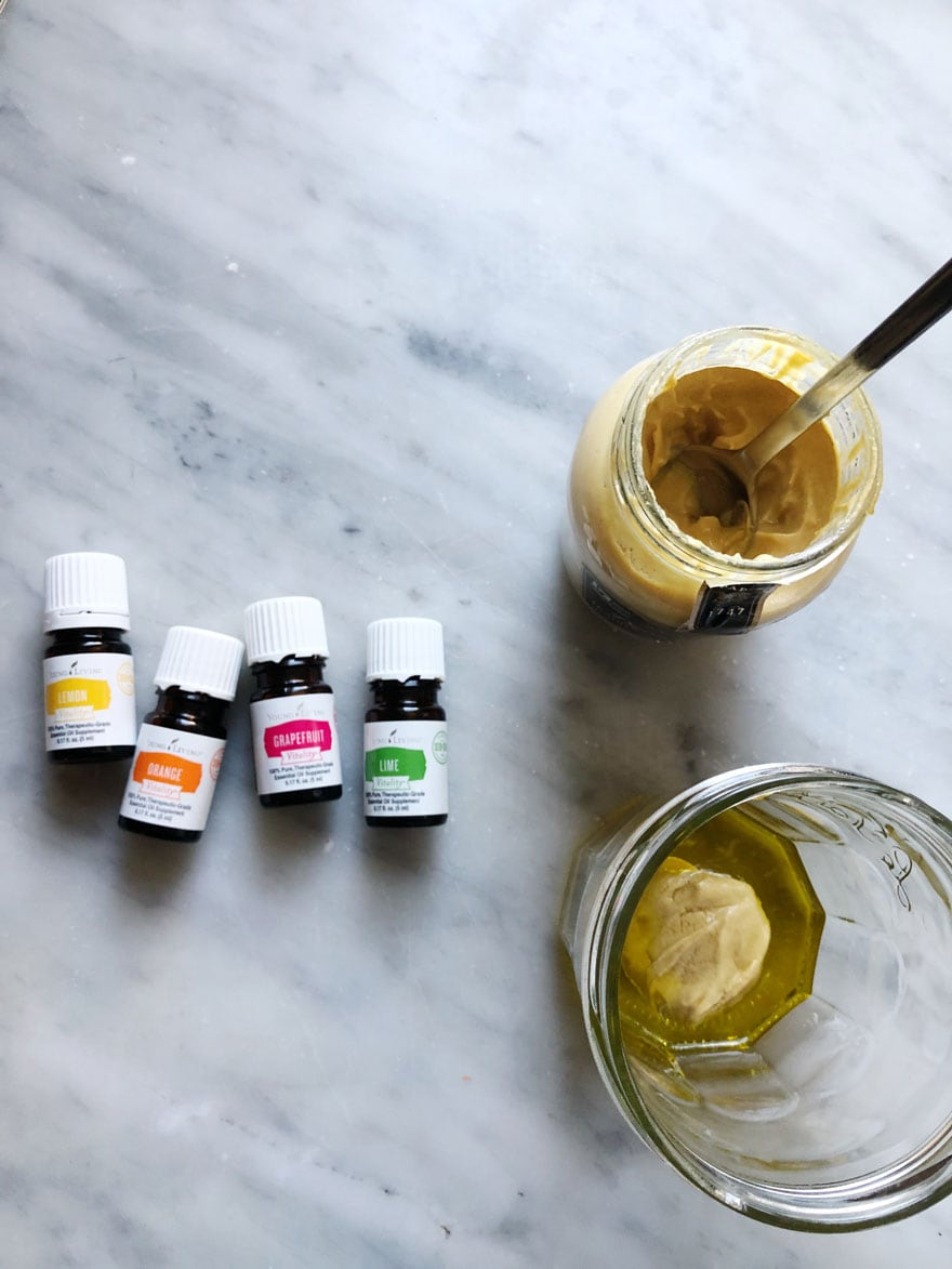 essential oil bottles, jar of mustard with a spoon in it, jar with olive oil and mustard