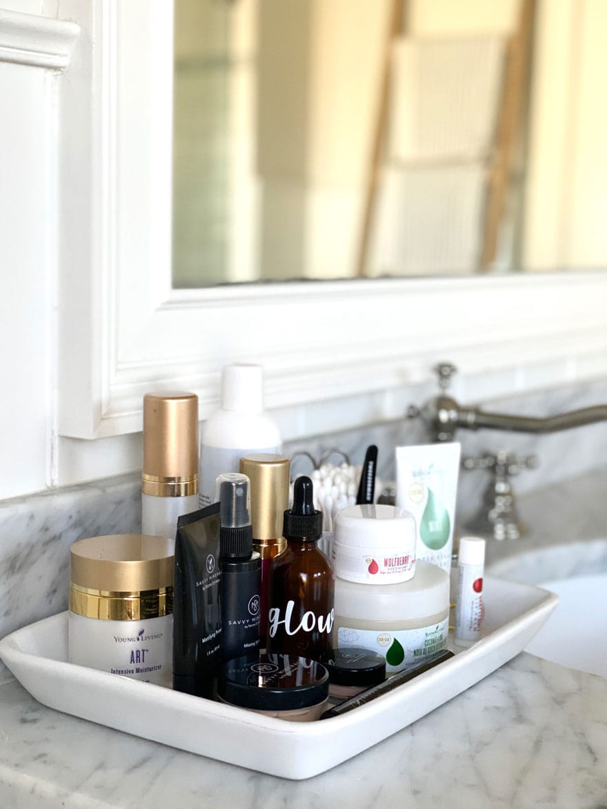bottles, makeup, moisturizer in a bathroom on marble counter in white ceramic tray