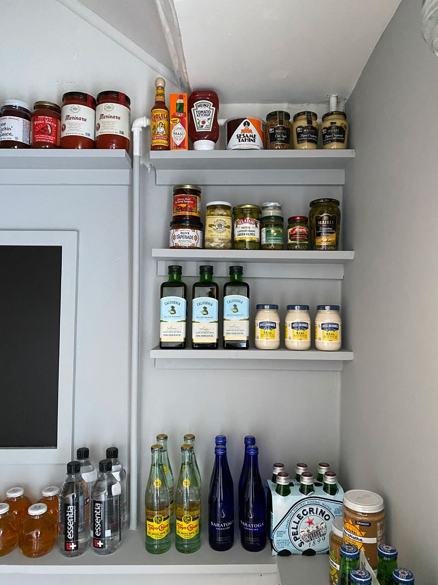 narrow shelves lined with bottles, jars of food in a pantry painted light gray