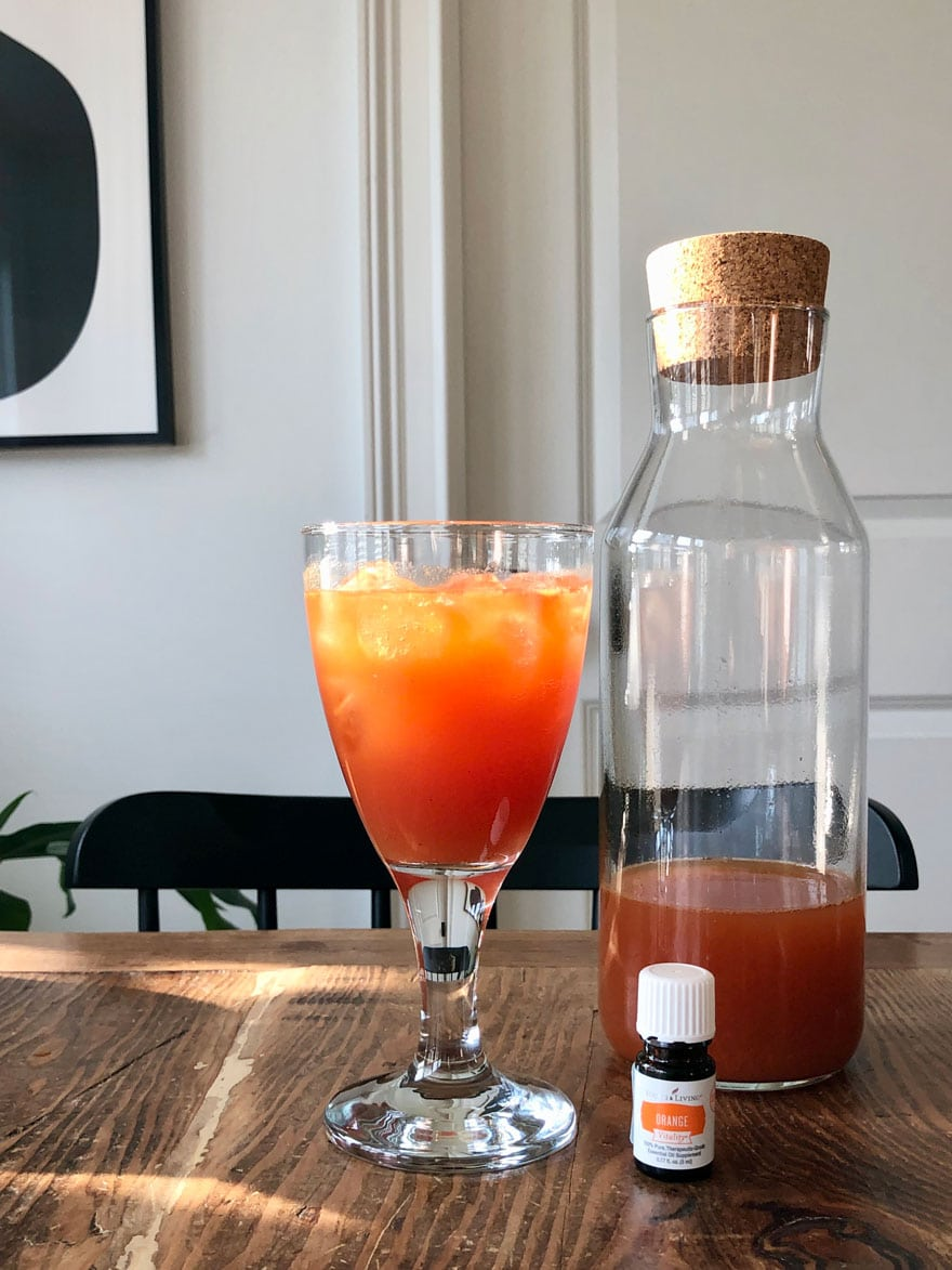 red orange drink on table with glass bottle and bottle of essential oil