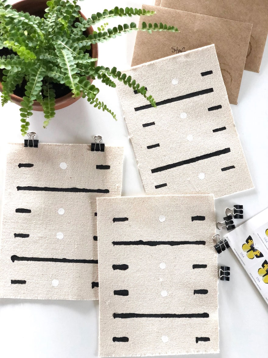 canvas pieces with black and white paint with small plant
