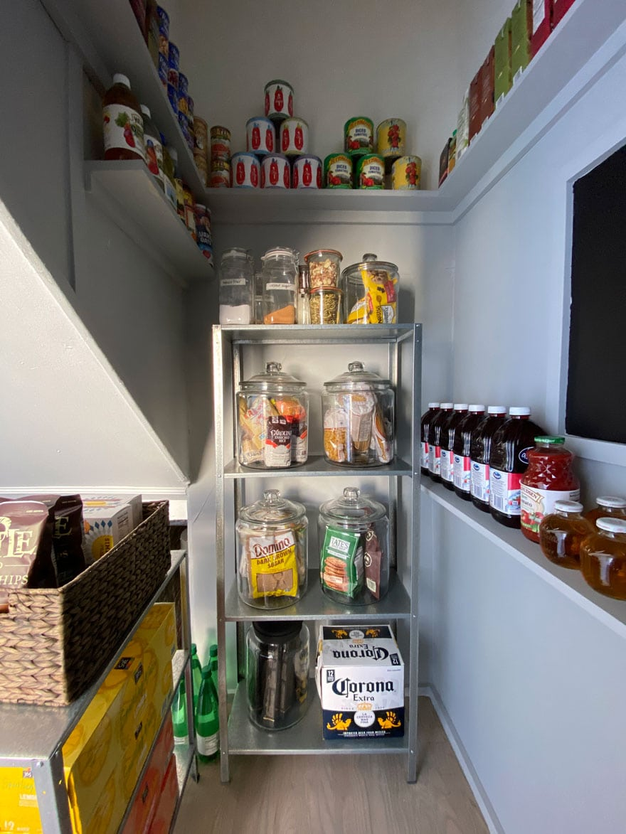 a metal shelf against a gray wall with hardwood floors in a pantry with food and jars of food