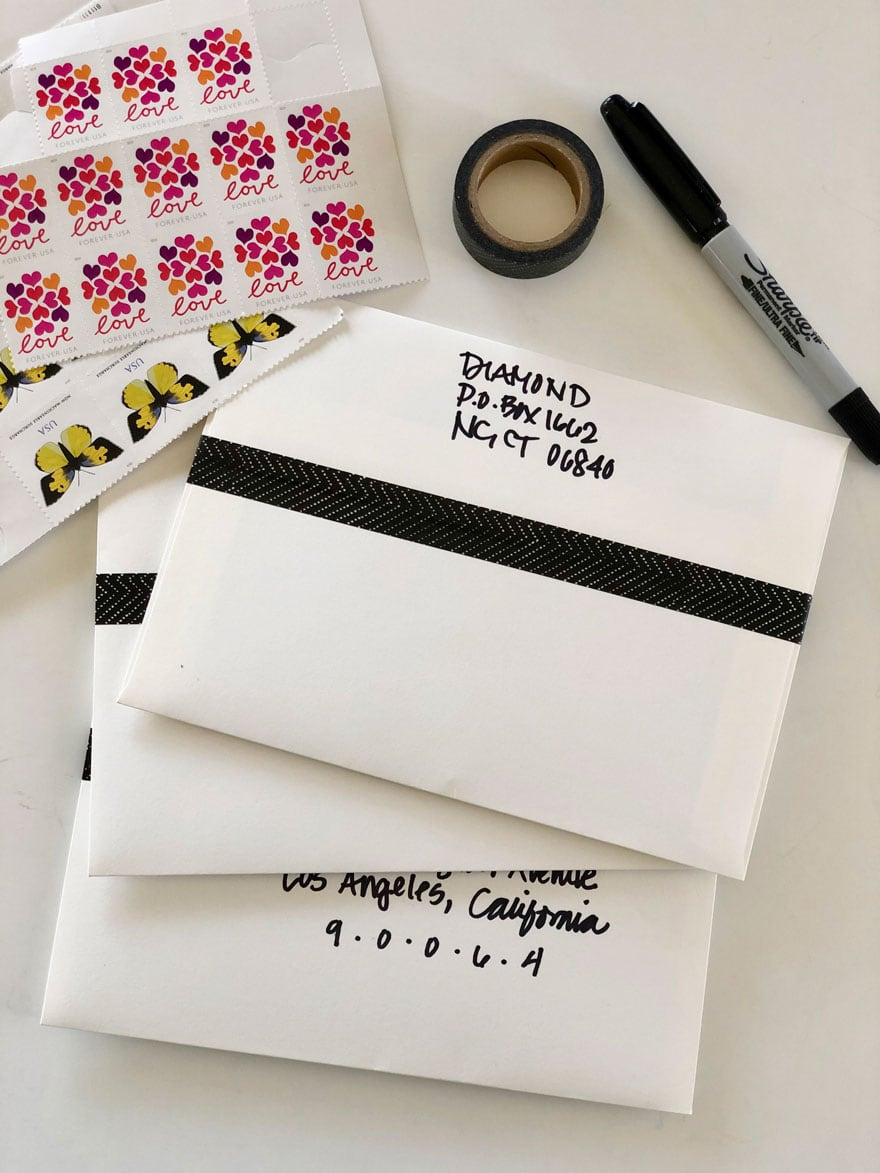 envelopes, stamps, tape, pen