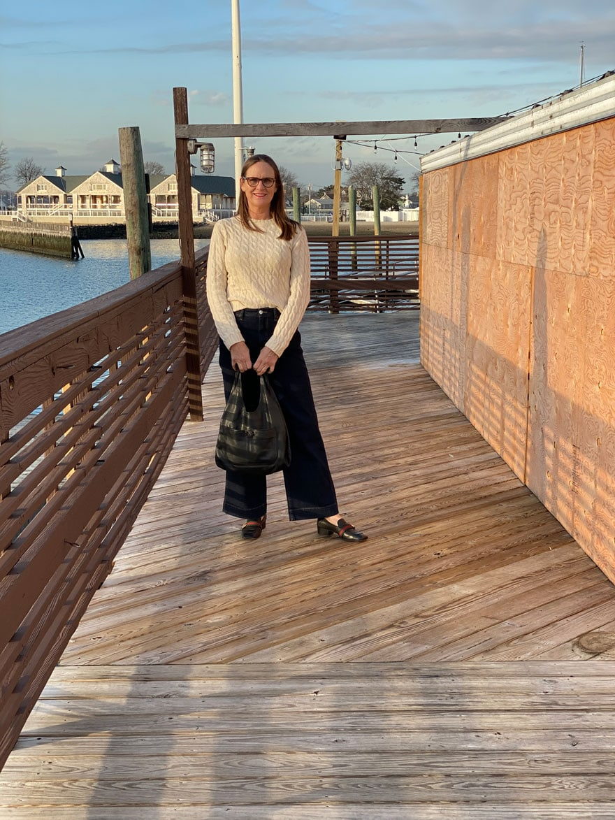 woman standing on dock near plywood b=wall in jeans and sweater holding purse