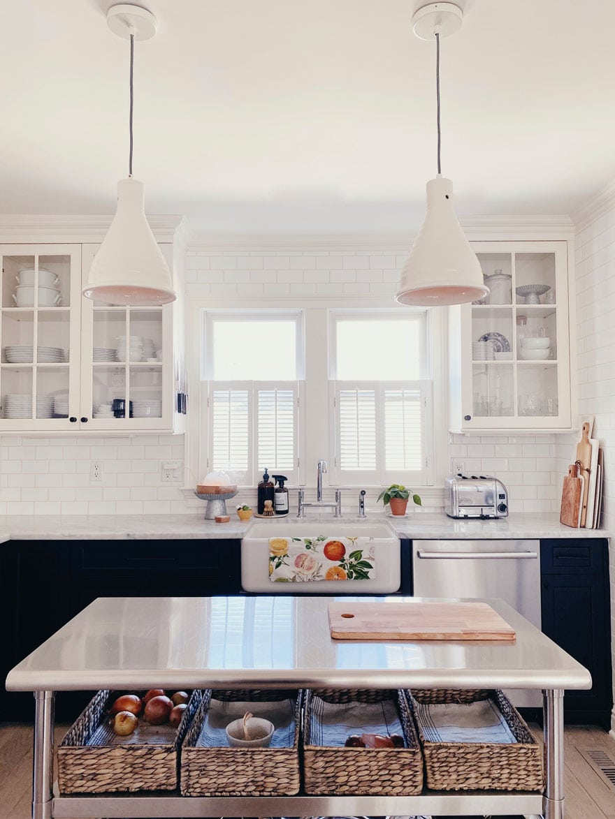 black and white kitchen with a stainless work table and two pendant light above