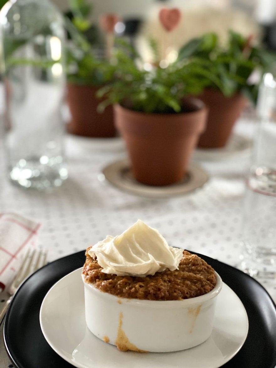 carrot cake in ramekin on table with three plants