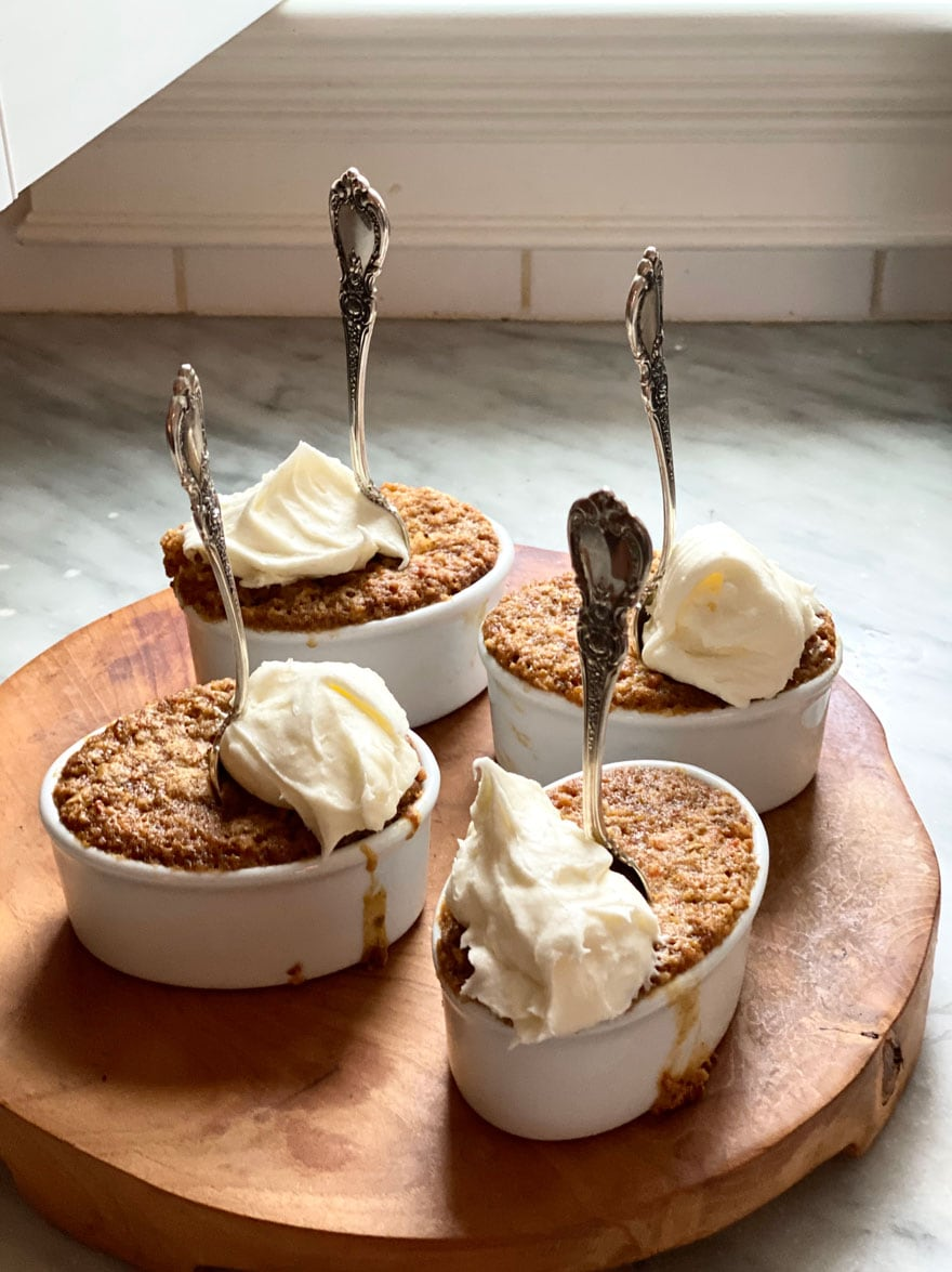 4 ramekins with cake and frosting with a spoon in each on a wood round board