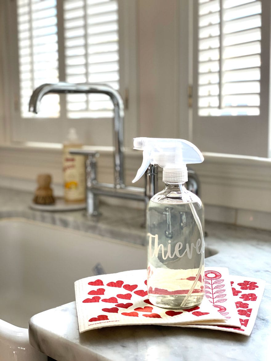 glass bottle with red and white dishcloths, sink, faucet
