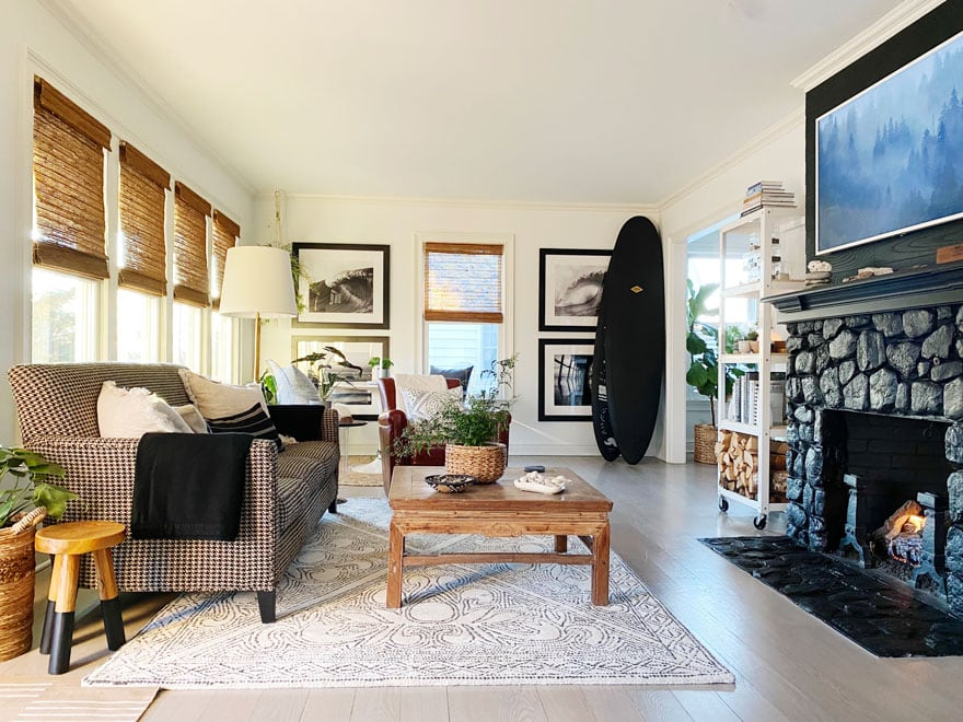 living room with windows, sofa, black surf boards and prints on walk, coffee table, chair, black stone fireplace