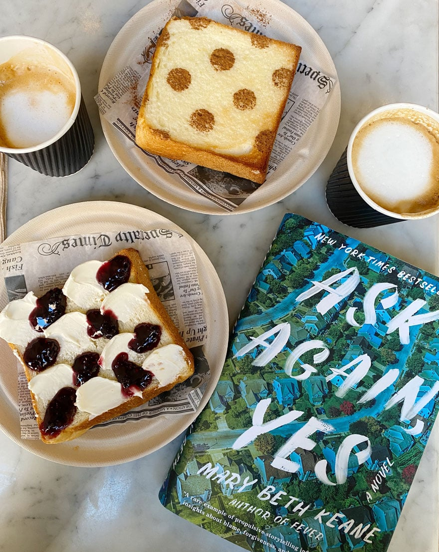copy of book, Ask Again, Yes and coffee cups and toast on plates on marble table top
