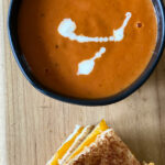 small black bowl of tomato soup with grilled cheese on wood board