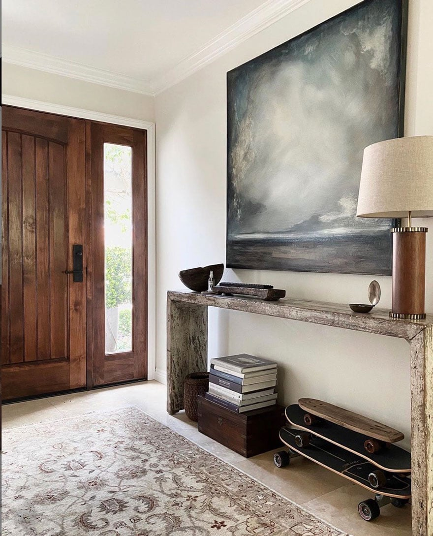 entryway table with lamp, painting, door