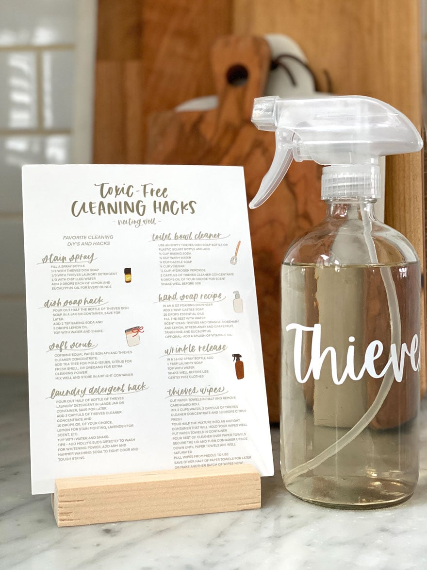card in wood holder with glass bottle of Thieves