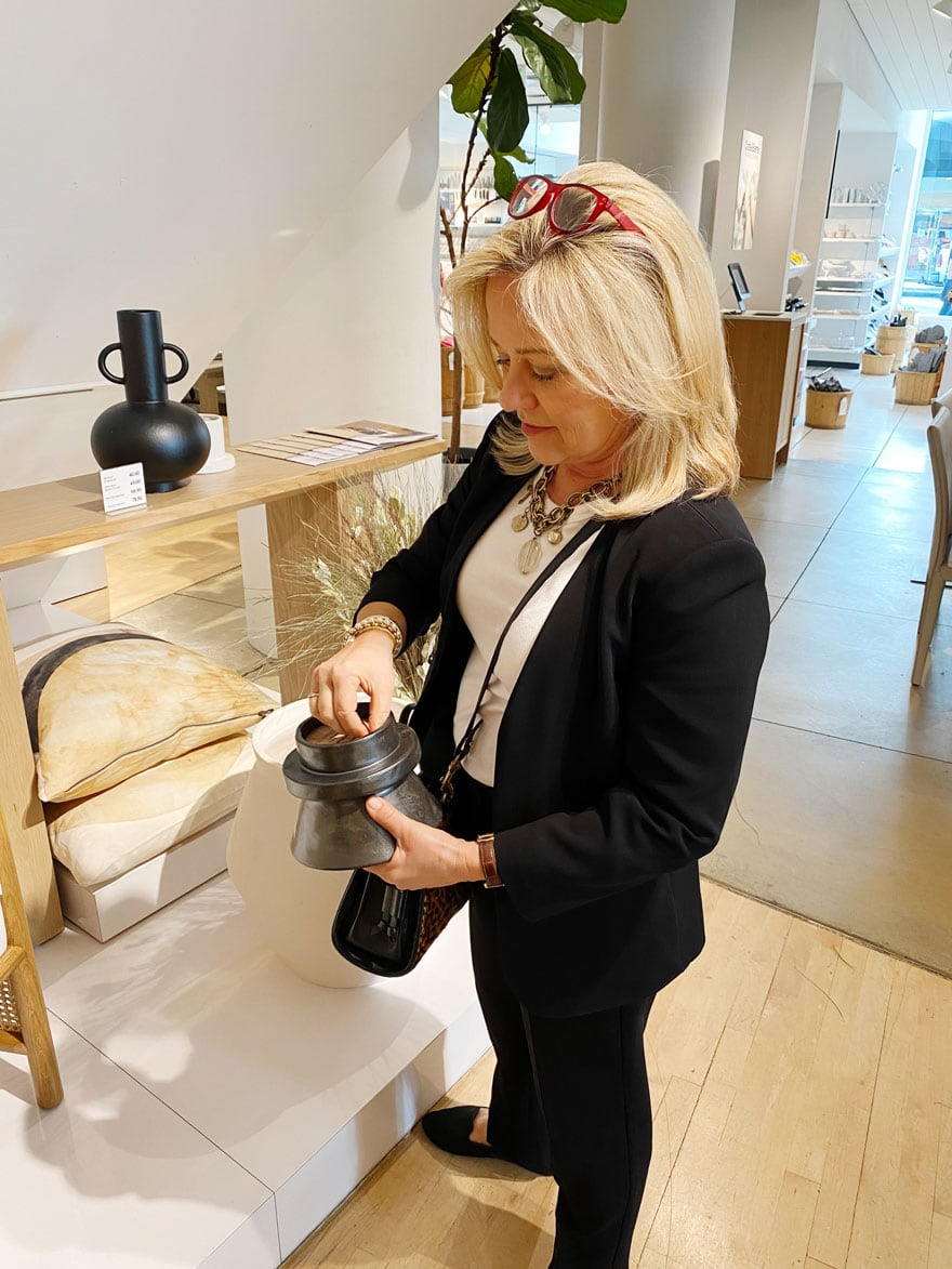 woman in black suit holding candle at a store