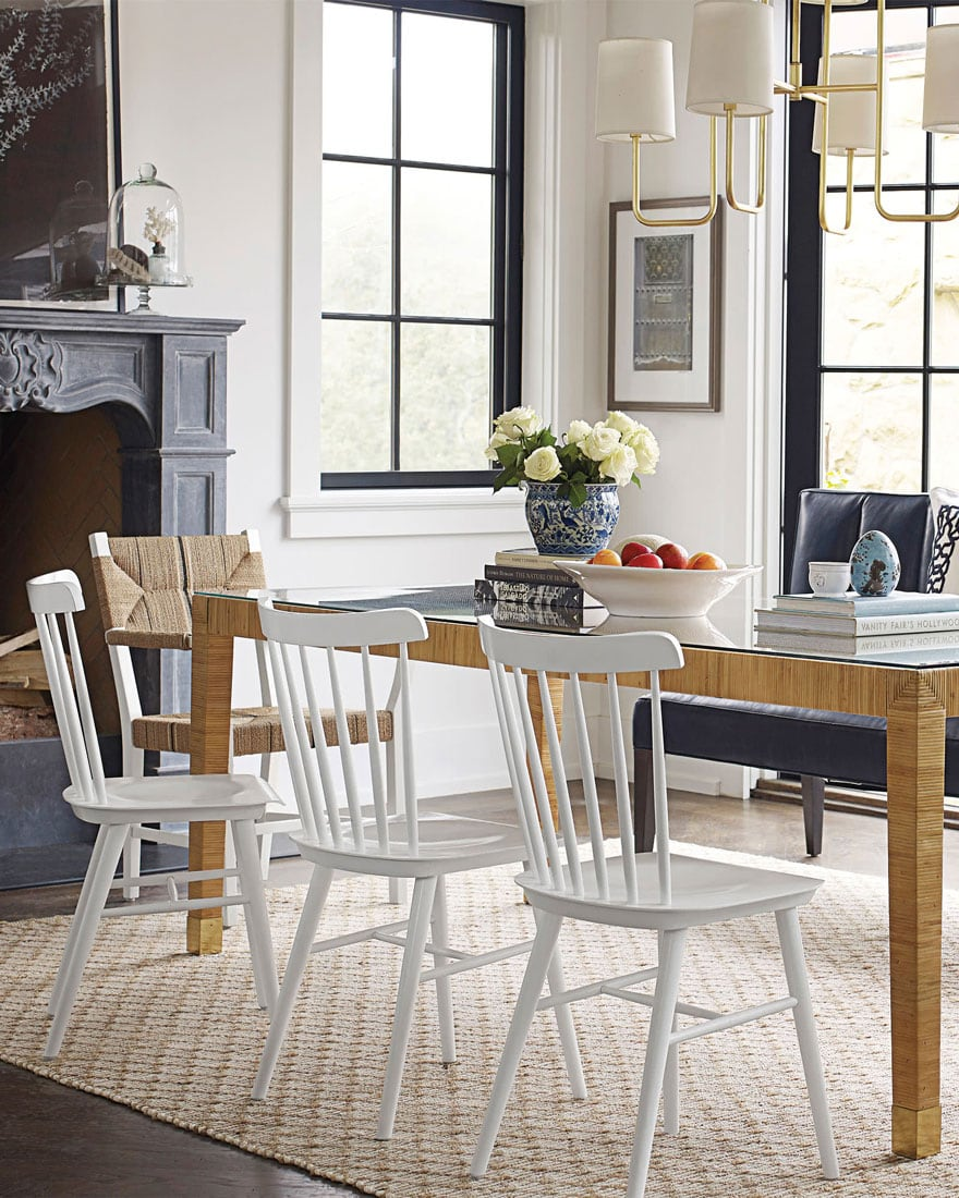wicker table with white dining chairs in dining room with ornate fireplace
