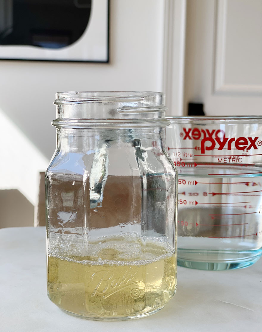 jar with light yellow liquid and glass Pyrex measuring cup