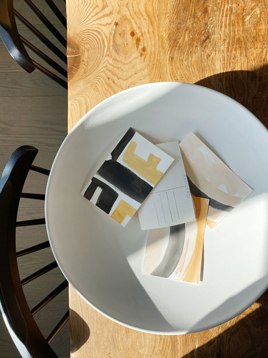 white shallow bowl with cards on table and chairs