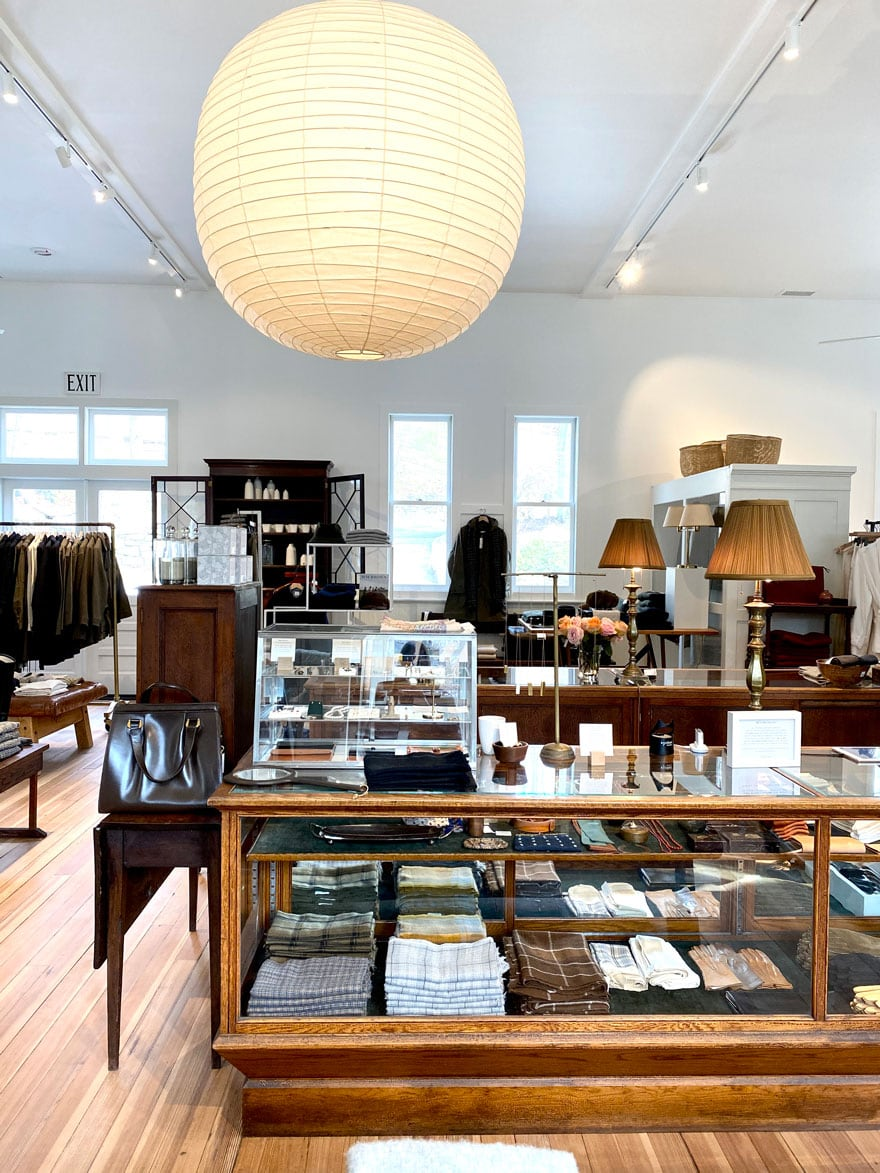 shop with large pendant, glass and wood display cases, art, white walls