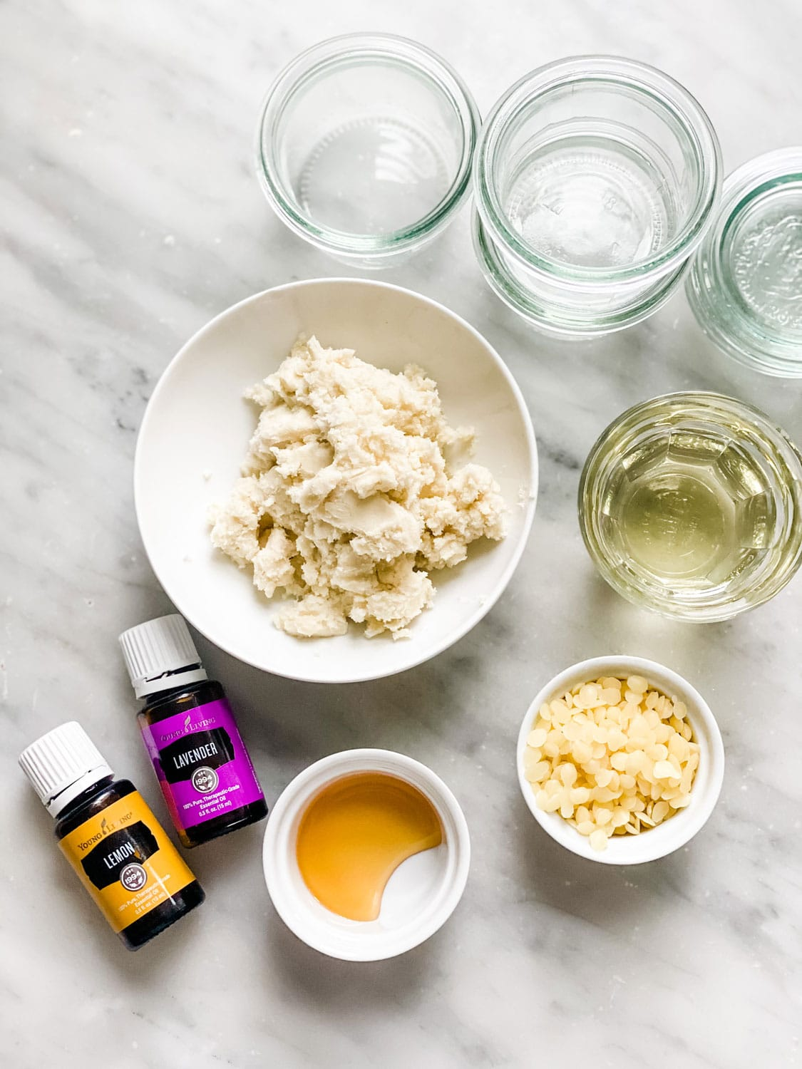 essential oil bottles, ingredients in small bowls on marble counter