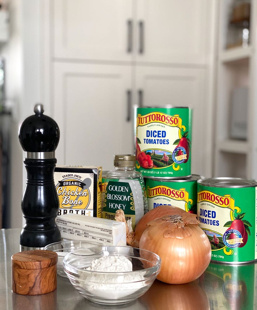 ingredients on counter, tomato cans, onions, pepper grinder