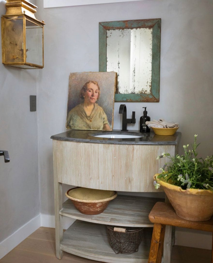 bathroom vanity, stool with plant, painting, mirror, lantern sconce on wall