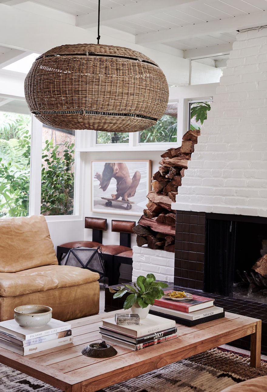 painted brick fireplace, stacked wood, books on table, pendant