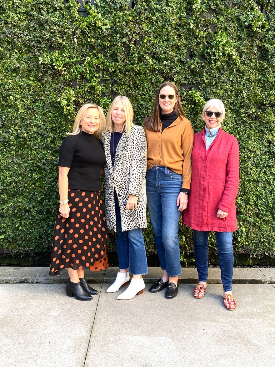 4 women standing against ivy covered wall
