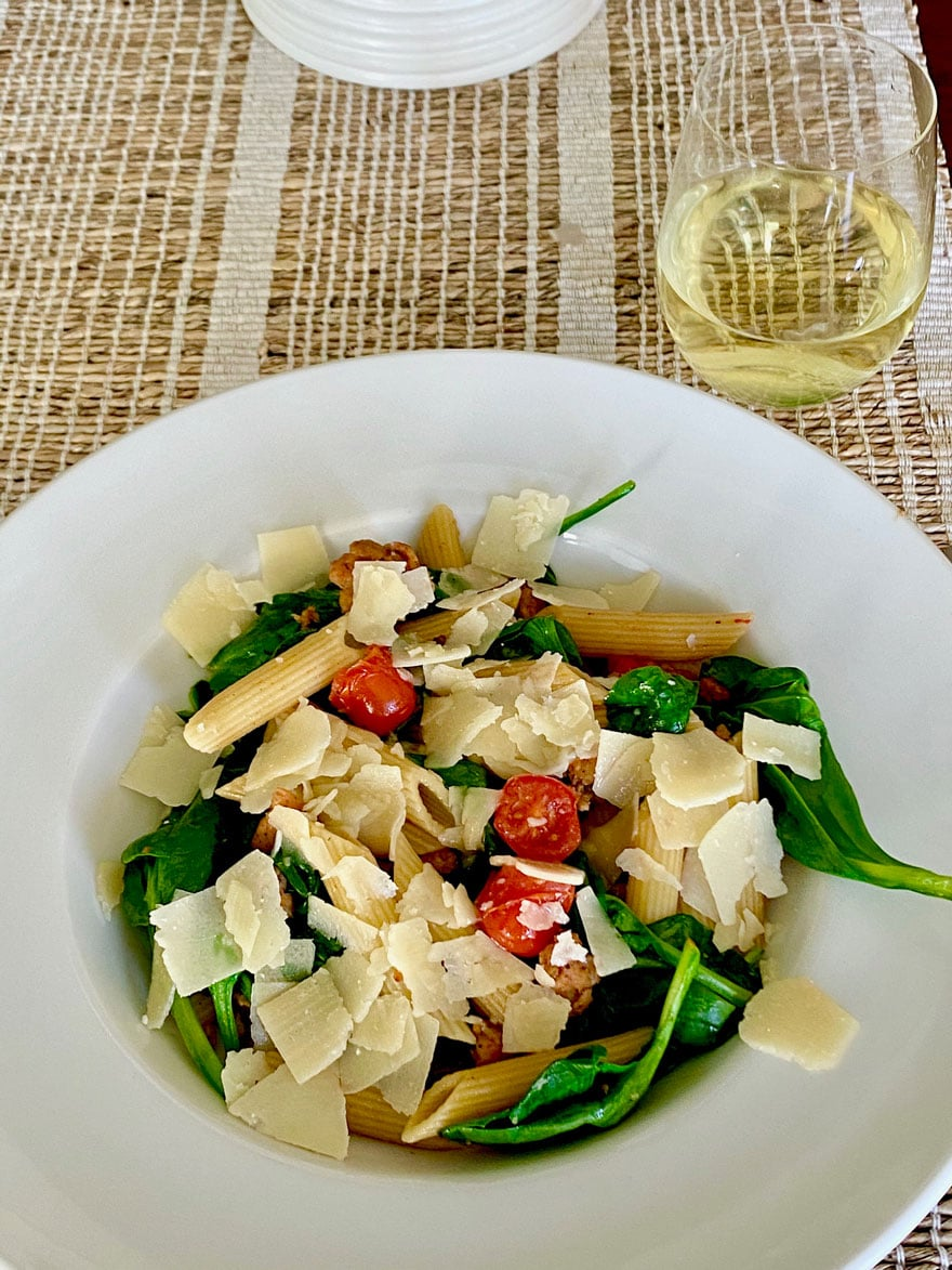 white bowl with pasta, spinach tomatoes and a glass of white wine
