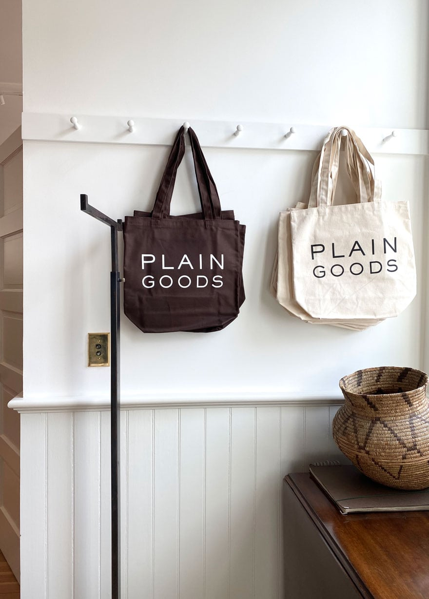 brown and cream tote bags with Plain Goods logo on white wall and shaker pegs, basket