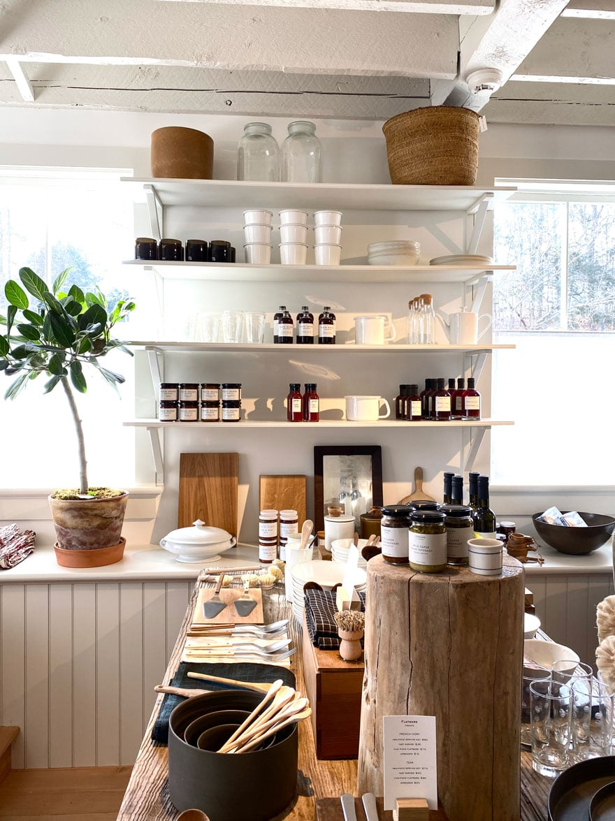 plant in window, open shelving with food, kitchen items, table with kitchen items