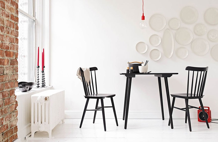 black chairs, table, white plates on white wall, white floors, red candles