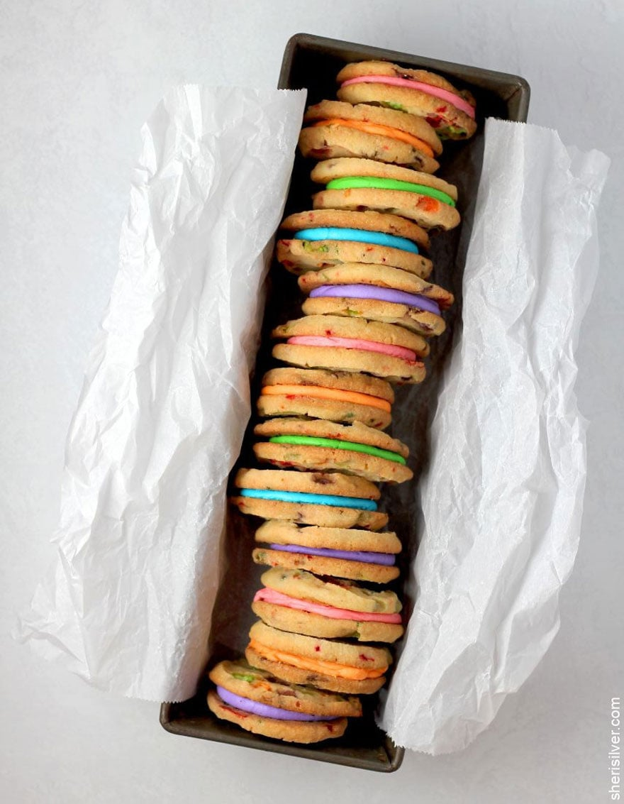 colorful sandwich cookies in a row inside a box with tissue paper