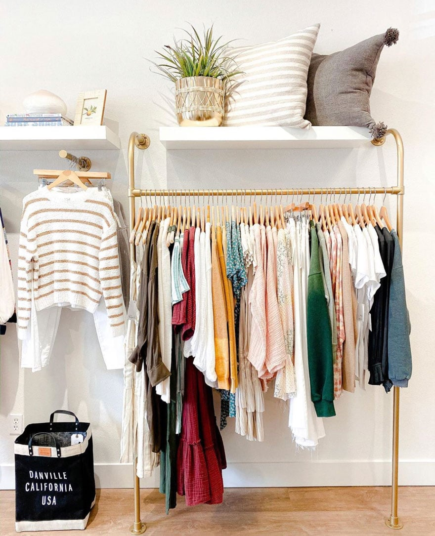clothing on copper bars, white walls, wood floors, black bag
