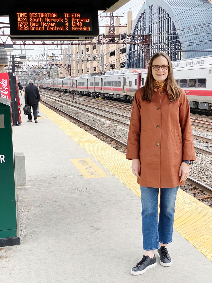 woman wearing jeans and coat standing on train platform with sign in background