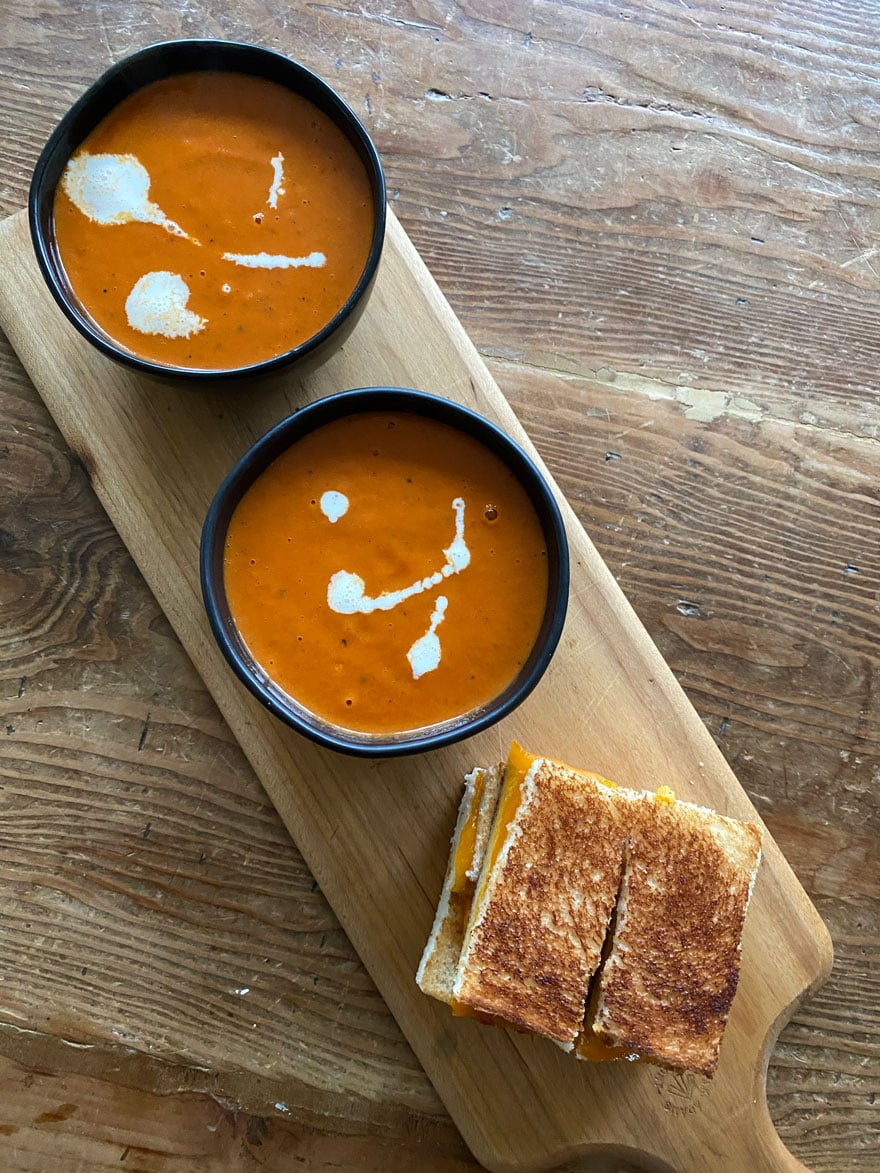 tomato soup in black bowls on wood board with grilled cheese sandwich