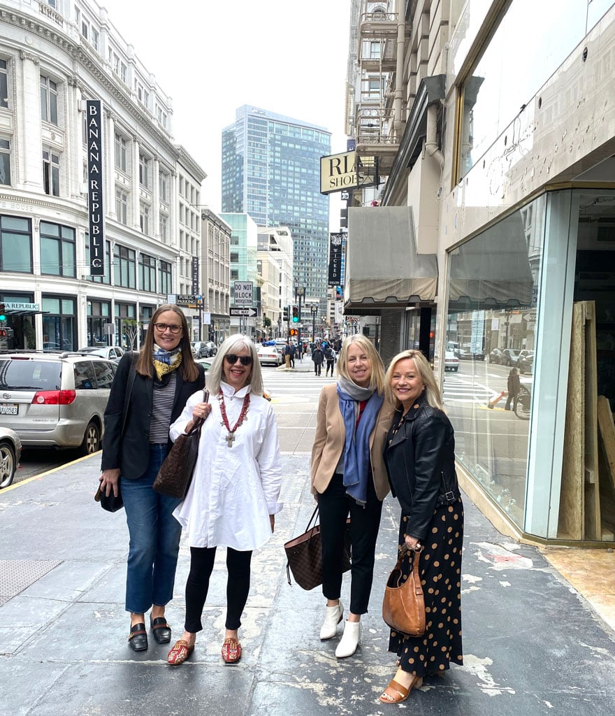 4 women on sidewalk in urban setting