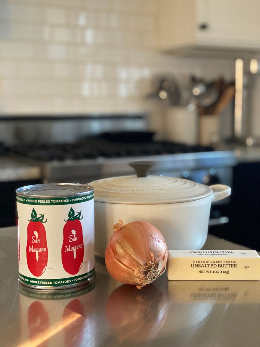 can of san Marzano tomatoes, onion, stick of butter, le crest pan with lid on counter