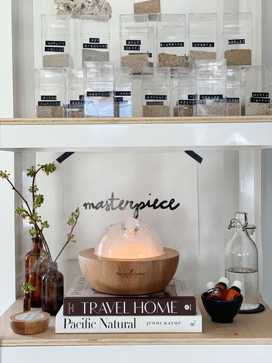 aria diffuser on shelf with branches in amber bottles, clear boxes with sand collection and labels
