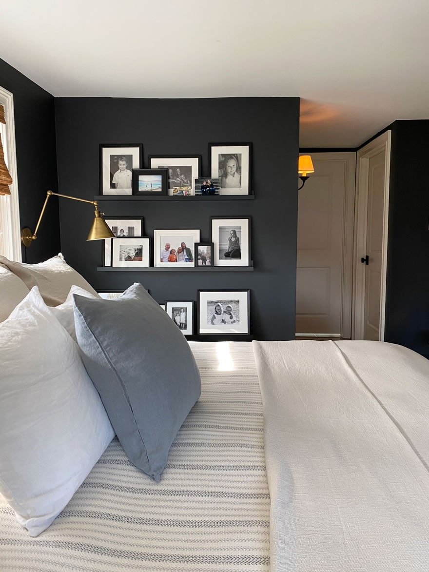 bbed with square pillows and photos on ledge with black walls
