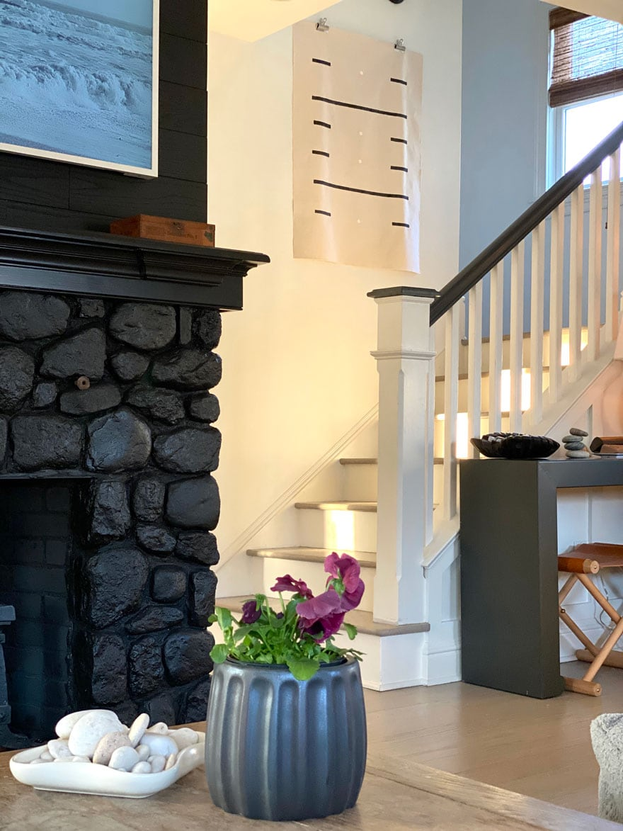 a black painted stone fireplace and a shot of the stairway with a canvas wall hanging